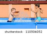 Two excited boys splashing in swimming pool - stock photo