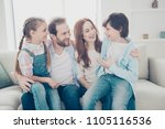 Small photo of Portrait of full family enjoying free time indoor hugging, schoolboy telling news story to mum daddy and sister, kids sitting on parent's legs. Understanding support trust idyllic concept