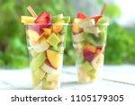 fruit salad in plastic cups... | Shutterstock . vector #1105179305