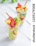 fruit salad in plastic cups... | Shutterstock . vector #1105179308