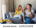 Young Couple Sitting On Sofa A...