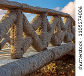 Small photo of Wooden fence made of palm trunks with partly cloudy sky in sunrise time in summer time