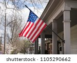 Small photo of American flag on a tradicional white woof building in the United States