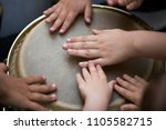 Children playing together at djembe drum, close up