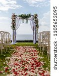 Stock photo wedding arch near the ocean for a ceremony decorated with white fabric and fresh flowers chairs 1105653095