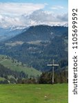 Small photo of Crucifix (cross) on mount rigi in focus in the foreground with alps in the background