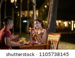 Small photo of Profile view of smiling young man entertaining his pretty girlfriend with light chatter while having dinner at beach restaurant of tropical resort