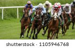 Stock photo head on view of galloping race horses and jockeys racing 1105946768