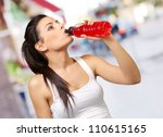 Stock photo portrait of young sporty woman drinking isotonic drink at street 110615165