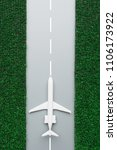 Small photo of Top view of toy white plane placed on airstrip with green artificial grass around