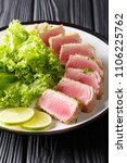 Small photo of Delicious steak ahi tuna in bread crumbs panko with lettuce and lime closeup on a plate on a black table. vertical