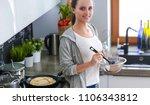 young woman prepares pancakes... | Shutterstock . vector #1106343812