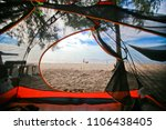 An Orange Tent On The Beach By...