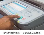 Small photo of man finger pressing the start button on a multifunction couler printer or copier.