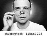 Stock photo youngster takes off his round glasses 110663225