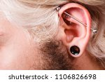 Small photo of Stretched lobe piercing, grunge concept. Pierced man ear with black plug tunnel. industrial and rook