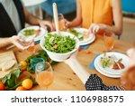 crop hand passing green salad... | Shutterstock . vector #1106988575