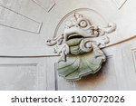 Small photo of fountain with sculpture of a scary fsh face in chinese style