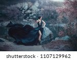 Small photo of The dark queen pose against the background of gloomy rocks. A luxurious black dress with a long train fluttering in the wind denuding her leg. Elegant, collected hairstyle with a gothic crown.