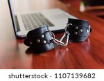 black leather handcuffs at table | Shutterstock . vector #1107139682