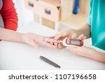 nurse hands using glucometer to ... | Shutterstock . vector #1107196658