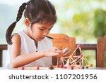 cute asian child girl playing... | Shutterstock . vector #1107201956