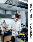 Shot Of Two Young Chefs In The...