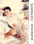 couple drinking prosecco in bed | Shutterstock . vector #1107463076