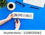 Small photo of Make the impossible possible. Cutting the part im of written word impossible by sciccors. Office desk. Blue background top view copy space