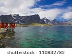 Typical norwegian fjord with fishing hut and high mountains peaks towering above the sea - stock photo