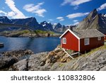 Traditional red fishing rorbu hut on Lofoten islands in Norway near bridge connecting islands - stock photo