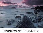 Lofoten islands under midnight sun with typical rocky coastline, on island of Vaeroy near Moskenesstraumen - stock photo