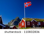Norwegian flag with typical norwegian red wooden house with sod roof on Lofoten islands - stock photo