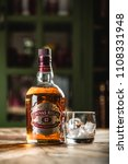 Small photo of MOSCOW/RUSSIA - APRIL 24, 2018: Chivas Regal whiskey bottle and glass with ice cubes on wooden table in dark bar. Chivas Regal is famous brand of Scotch aged popular whiskey