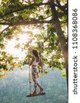 young girl hanging on swings in ... | Shutterstock . vector #1108368086