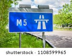 A blue motorway sign directs drivers and traffic onto the M5 motorway in England, United Kingdom.