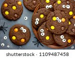 Small photo of Halloween cookies, chocolate american cookies with candy eyes and chocolate orange and yellow candy dragee, halloween treats for kids