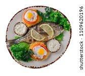 Small photo of delicious fried dorado or bream of gilt head with lemon, eggs, spices and fresh rosemary, top view, close-up on white background