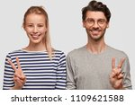 Small photo of Happy young couple smile and gesture vsigns, being in high spirit, make photo for long memory, enjoy vacation together, dressed in casual sweaters isolated on white wall. Woman and man show peace sign
