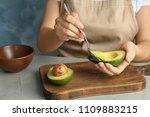 woman scooping ripe avocado...   Shutterstock . vector #1109883215