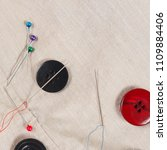 Small photo of Buttons, pins and needles with threads on cotton close up