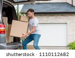 Small photo of strenuous young man moving boxes from car into new house