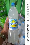 Small photo of Klang, Malaysia - June 8, 2018 : Hand hold REVIVE isotonic carbonated drink bottles on store shelf.