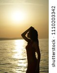 woman silhouette by sunset on... | Shutterstock . vector #1110203342