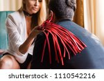 woman put whip on man shoulder | Shutterstock . vector #1110542216