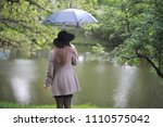 young girl in a coat in a... | Shutterstock . vector #1110575042