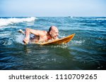 a senior man on a surfboard | Shutterstock . vector #1110709265
