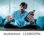 Small photo of drunk alcoholic lain business man drinking whiskey from the bottle and glass depressed wasted and sad at home couch in alcohol abuse and alcoholism concept
