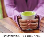 Female Hand Holding A Cup On...