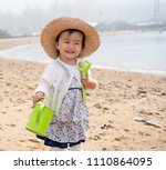 asian baby playing by the beach | Shutterstock . vector #1110864095